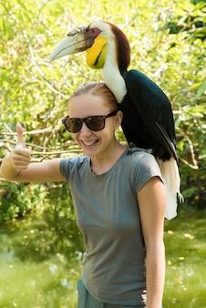 Uccello esotico su una spalla di un womans