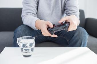 Un giovane che tiene il regolatore di gioco che gioca i videogiochi