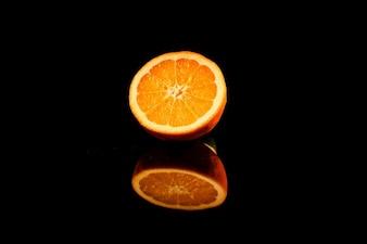 Un pezzo di arancia succosa si trova sul tavolino di vetro nero