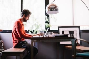 Uomo alla moda nell'ufficio creativo che lavora