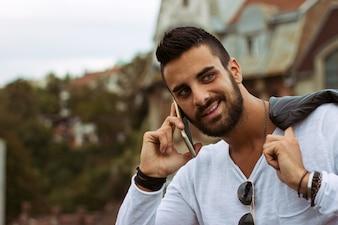 Uomo bello che comunica sul telefono all'aperto. Con giacca di pelle, occhiali da sole, un ragazzo con la barba. Effetto Instagram