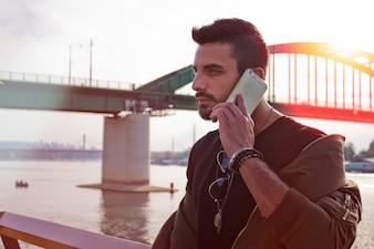 Uomo bello che comunica sul telefono all'aperto. Con giacca, occhiali da sole, un ragazzo con la barba. Effetto Instagram