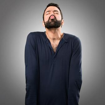 Uomo bello con barba che trasmette un bacio su sfondo grigio