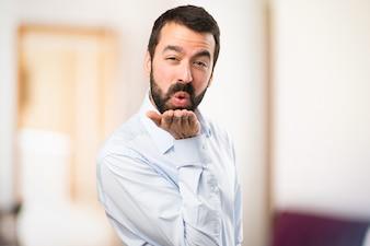 Uomo bello con barba che trasmette un bacio su sfondo unfocused