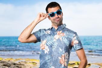 Uomo bello con camicia da fiori con occhiali da sole in spiaggia