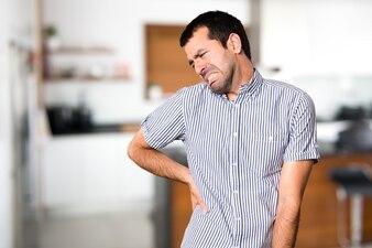Uomo bello con il mal di schiena all'interno della casa