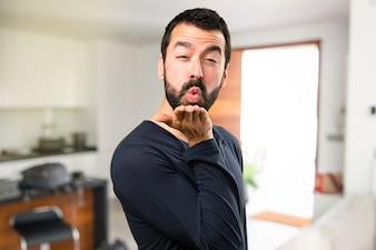 Uomo bello con la barba che trasmette un bacio all'interno della casa