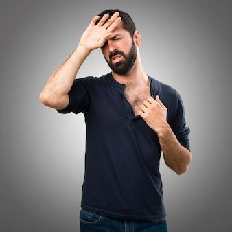 Uomo bello con la barba con la febbre su sfondo grigio