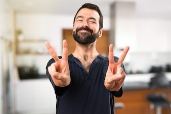 Uomo bello con la barba facendo vittoria gesto all'interno della casa