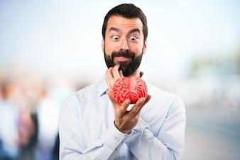 Uomo bello con la barba in possesso di un cervello su sfondo unfocused