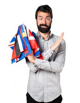 Uomo bello con la barba tenendo molte bandiere e facendo nessun gesto