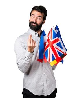 Uomo bello con la barba tenendo molte bandiere e fare gesto di denaro