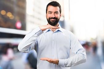 Uomo bello con la barba tenendo qualcosa su sfondo unfocused
