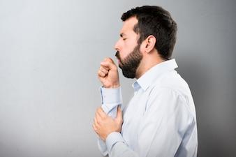 Uomo bello con la barba tosse molto su sfondo testurizzato
