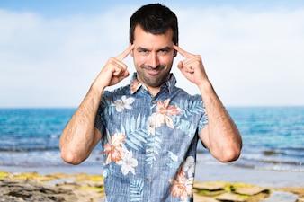Uomo bello con la camicia di fiori che pensa alla spiaggia