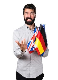Uomo bizzarro frustrato con la barba tenendo molte bandiere