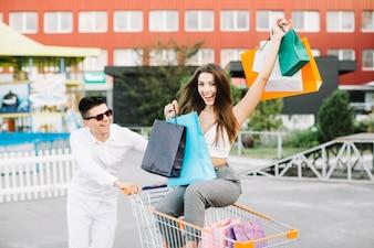 Uomo che guida carrello di acquisto con la donna felice