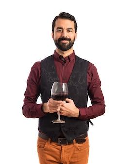 Uomo che indossa il panciotto che tiene un bicchiere di vino