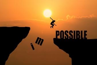 Uomo che salta impossibile o possibile sopra scogliera sullo sfondo del tramonto, idea di business concept