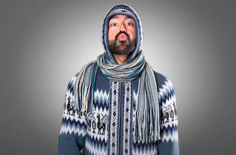 Uomo con abiti invernali che trasmette un bacio su sfondo grigio