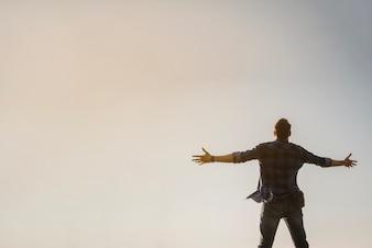 Uomo con braccia aperte guardando il cielo
