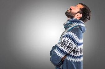 Uomo con i vestiti invernali che osservano su priorità bassa grigia