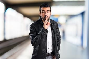 Uomo con rivestimento in pelle gesticolare silenzio su sfondo unfocused