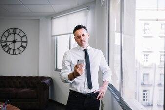 Uomo d'affari arrabbiato guardando lo smartphone