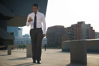 Uomo d'affari che cammina e legge messaggio sul telefono