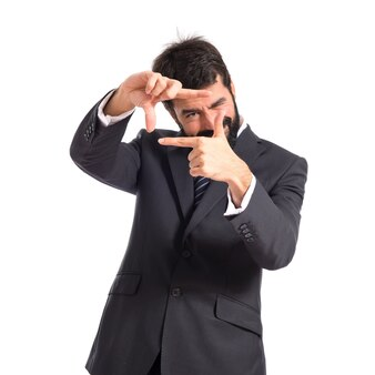 Uomo d'affari concentrando con le dita su uno sfondo bianco