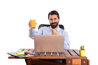 Uomo d'affari nel suo ufficio bere succo d'arancia