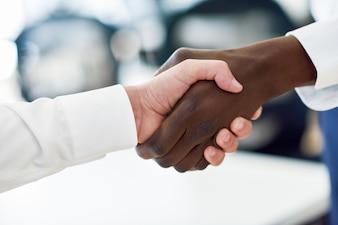 Uomo d'affari nero stringe la mano con un caucasico