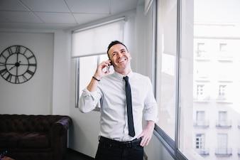 Uomo d'affari sul telefono ridendo