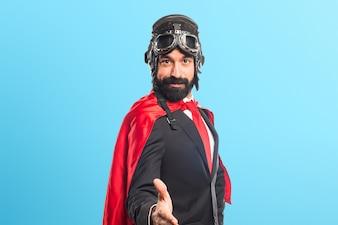 Uomo d'affari super eroe fare un affare su sfondo colorato
