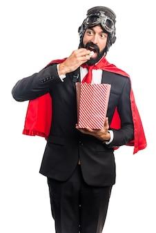 Uomo d'affari super eroe mangiare popcorn