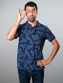 Uomo di Brunette con gli occhiali su sfondo grigio