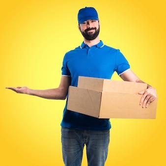 Uomo di consegna presentando qualcosa su sfondo colorato