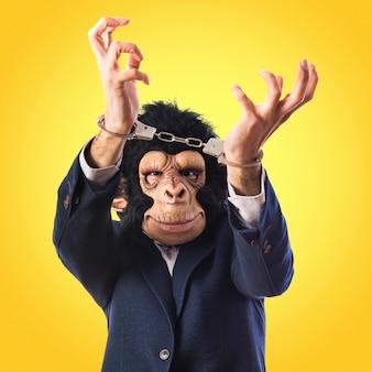 Uomo di scimmia con le manette su sfondo colorato
