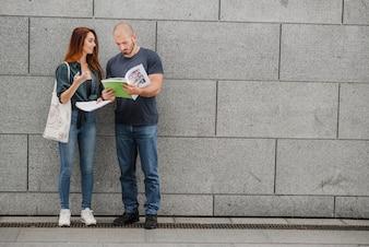Uomo e donna in piedi contro la parete grigia