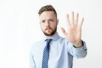 Uomo gravi di affari che mostra il gesto di arresto
