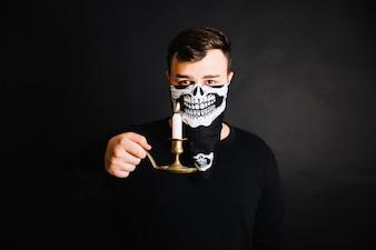 Uomo in maschera di scheletro in posa con la candela