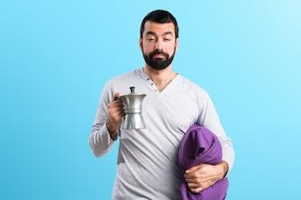 Uomo in pigiama in possesso di un piatto di caffè su sfondo colorato
