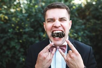 Uomo in posa con coni di pino in bocca