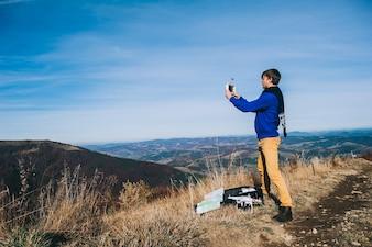 Uomo in possesso di un drone per la fotografia aerea. silhouette contro il cielo di tramonto