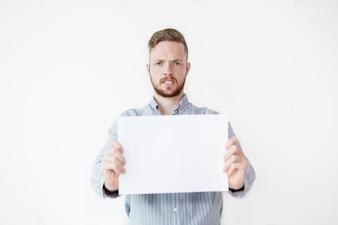 Uomo irritato che tiene foglio di carta in bianco