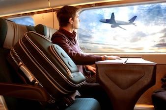 Uomo seduto in un treno guardando un airplain