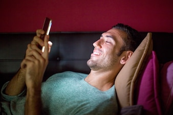 Uomo sorridente utilizzando smartphone sul divano a notte