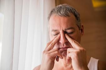 Uomo triste e depresso che tiene la testa con la mano, in piedi accanto alla finestra. L'uomo tiene la zona del naso e del seno con le dita in un dolore ovvio da un mal di testa nella parte anteriore della fronte