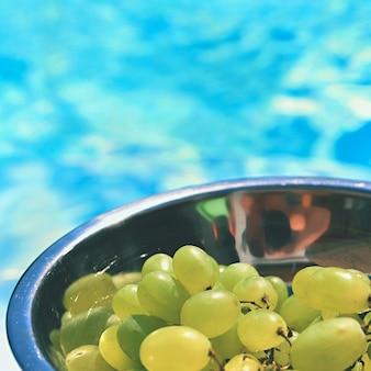 Uva in una ciotola con uno sfondo di acqua blu