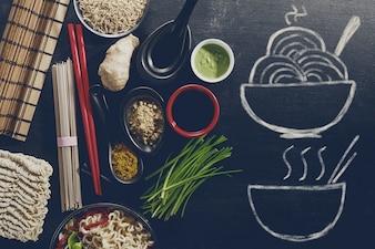Varietà diversi ingredienti per la cottura gustoso asiatico asiatico alimentare con mano disegnata piatto pronto sulla lavagna. Vista superiore con lo spazio di copia. Sfondo scuro. Sopra.